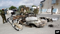 FILE - Somali soldiers stand near the wreckage of car bomb that was detonated at the main gate of the presidential palace in Mogadishu, July, 9, 2014.