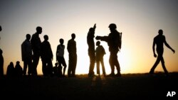 FILE - A French soldier checks passengers of a transport truck arriving in Gao, northern Mali, Feb. 14, 2013.