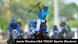 "Joki ""American Pharoah"" Victor Espinoza merayakan kemenangan dalam Kentucky Derby ke-141 di Churchill Downs, 2 Mei 2015. (Jamie Rhodes-USA TODAY Sports)"