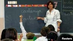 FILE- A teacher points to a blackboard with words in Catalan and in Spanish during a language class at a public school in El Masnou, near Barcelona, Spain.