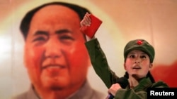 "FILE - A Chinese, dressed as a Red Guard and holding a ""Little Red Book"" (quotations of Chairman Mao), performs in front of a portrait of the late Chairman Mao Zedong at a restaurant named ""Red Classic"" in Beijing."