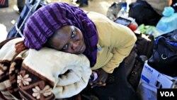 Seorang pekerja migran dari Nigeria yang melarikan diri dari kekacauan di Libya menunggu di penyeberangan Ras Jdir, perbatasan Libya dan Tunisia.
