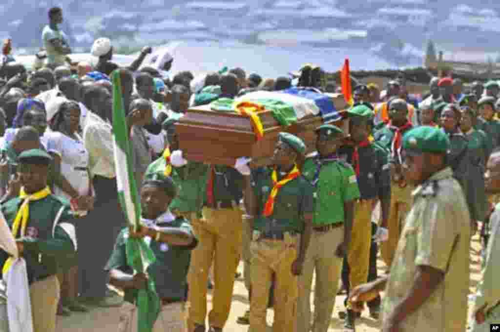 Jama'a na kallo a yayin da 'yan kungiyar agajin Boys Scouts ke dauke da akwatunan gawarwakin wadanda aka kashe a harin.