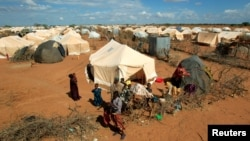 FILE - Refugees stand outside their tent at the Ifo Extension refugee camp in Dadaab, near the Kenya-Somalia border, Oct. 19, 2011.