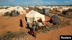 FILE - Refugees stand outside their tent at the Dadaab camp near the Kenya-Somalia border, Oct. 19, 2011. The Dadaab camp has hosted hundreds of thousands of Somali refugees for decades.
