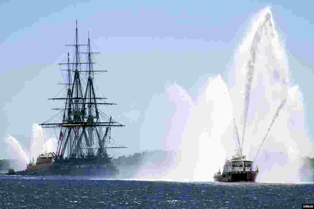 Chiến hạm Mỹ USS Constitution được hộ tống bởi tàu chữa cháy đang tiến vào vùng biển Boston, tiểu bang Massachusetts.