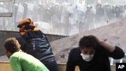 ພວກປະທ້ວງແລະຕໍາຫລວດແກວ່ງກ້ອນຫິນໃສາກັນ ໃນລະຫວ່າງການ ປະທະກັນທີ່ຈຸຕຸລັດ Tahrir ໃນໃຈກາງກຸງໄຄໂຣ, ອີຈິບ. ວັນທີ 23 ພະຈິກ 2011.