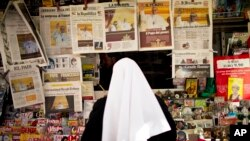 A nun looks at front pages showing newly elected Pope Francis at a newsstand near the Vatican, March 14, 2013.