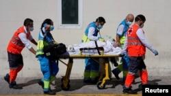 Petugas kesehatan mendorong tandu dengan pasien di unit gawat darurat di rumah sakit 12 de Octubre di tengah pandemi Covid-19, di Madrid, Spanyol, 2 September 2020.