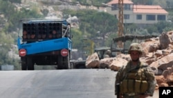 A Lebanese army soldier stands next of a rocket launcher placed on a pick up truck that was used by Hezbollah to fire rockets near Israeli positions, in the southeastern village of Shwaya, near the border with the Golan Heights, Friday, Aug. 6, 2021…