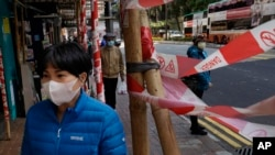 A woman wearing face mask walks on a street in Hong Kong Tuesday, Feb. 18, 2020. COVID-19 viral illness has sickened tens of thousands of people in China since December. (AP Photo/Vincent Yu)