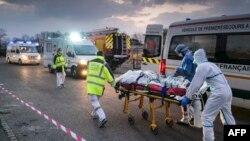 지난 29일 프랑스 뮐루즈의 군 병원에서 의료 관계자들이 신종 코로나바이러스 감염증(COVID-19) 확진자를 긴급 이송하고 있다.