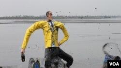 Ogoh-Ogoh Aburizal Bakrie Dilarung di Kolam Penampungan Lumpur Segabai Simbol Penyebab Bencana Kemanusiaan di Porong, Sidoarjo. (VOA/Petrus Riski)
