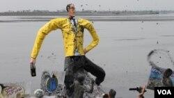 Ogoh-ogoh Aburizal Bakrie dilarung di kolam penampungan lumpur sebagai simbol penyebab bencana kemanusiaan di Porong, Sidoarjo. (VOA/Petrus Riski)