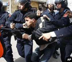 Moroccan police officers arrest a demonstrator during a protest against government policy in Casablanca, March 13, 2011