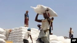 Para pekerja mengirimkan bantuan makan dari Program Pangan Dunia PBB di Aslam, Hajjah, Yaman, 21 September 2018.