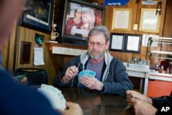 Wes Lewis plays cards with fellow regulars at the Frosty Freeze restaurant in Sandy Hook, Ky., Dec. 13, 2017.