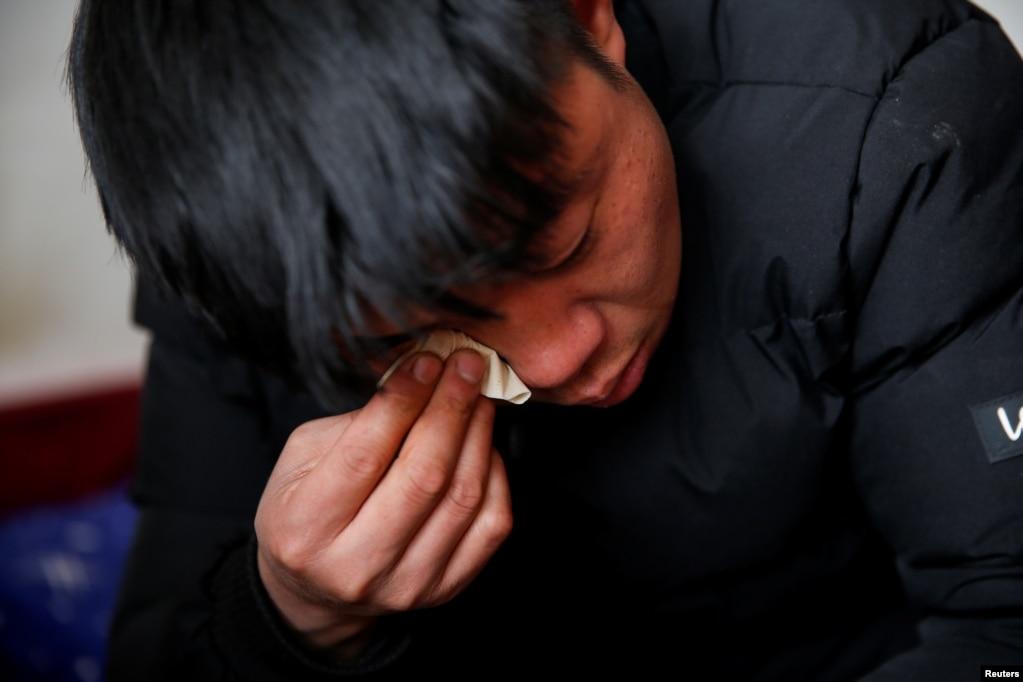 """33岁的杨念连(音)在北京打工,居住在京郊马驹桥小区,除夕年夜饭期间与老家通电话。他说:""""每次我回家,女儿最喜欢的事情就是和我聊天,她跑来跑去,听我讲在北京打工的所有事情。""""(2021年2月11日)(photo:VOA)"""