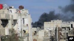 시리아 정부군의 포격으로 검은 연기가 치솟고 있는 중부 홈스주 바바 암르지역
