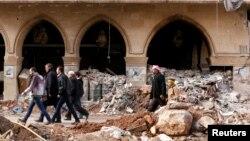 Người dân đi qua đống đổ nát của khách sạn Coral Julia Dumna ở Aleppo, ngày 17/12/2016.