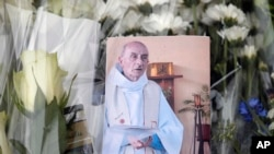 A picture of late Father Jacques Hamel is placed on flowers at the makeshift memorial in front of the city hall closed to the church where an hostage taking left a priest dead the day before in Saint-Etienne-du-Rouvray, Normandy, France, July 27, 2016.