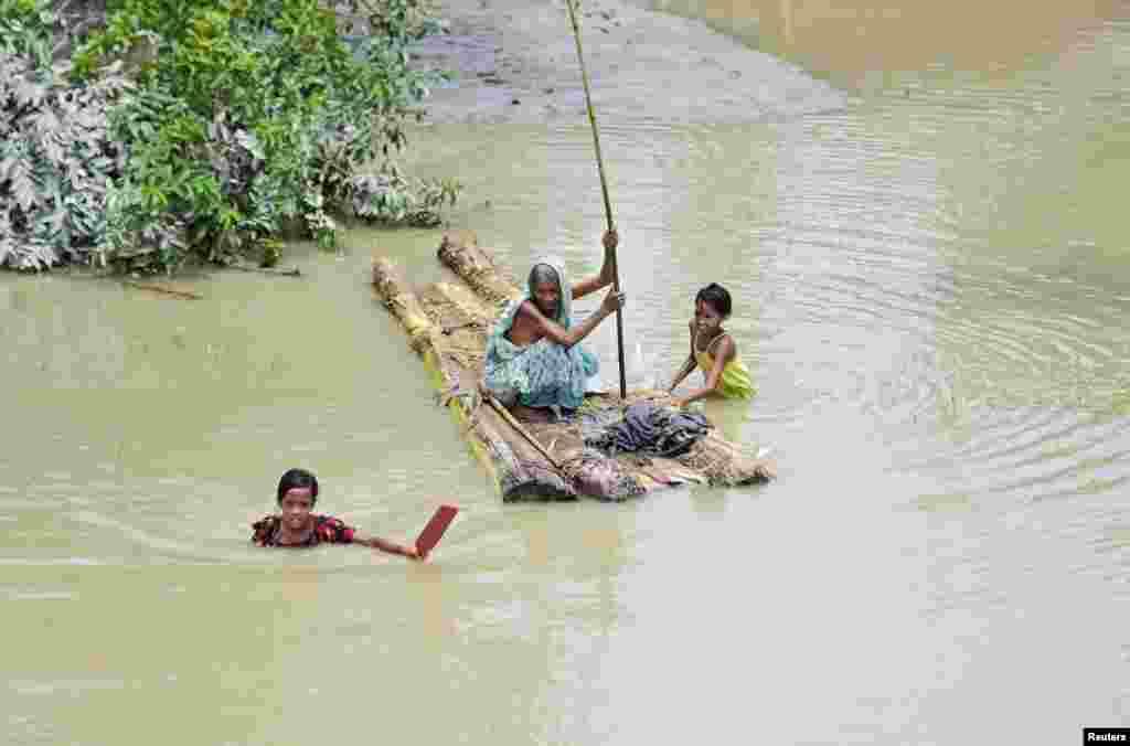 Seorang perempuan lansia mendayung rakit, sementara anak-anak perempuan berusaha melintasi banjir yang melanda desa Laharighat, distrik Morigaon, negara bagian Assam, India.