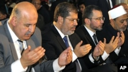Egyptian Vice President, Mahmoud Mekki, left, President Mohammed Morsi, second left, Prime Minister Hesham Kandil, third left, and the Grand Sheik of Al-Azhar, Ahmed el-Tayeb, right, attend Eid al-Fitr prayers to mark the start of a three-day Muslim holiday that signals the end of the holy month of Ramadan, Aug. 19, 2012.