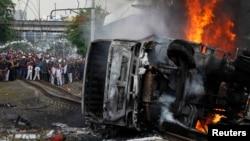 Warga menonton di lokasi tabrakan kereta KRL dan truk pengangkut BBM di Bintaro, Jakarta Selatan, Senin (9/12).