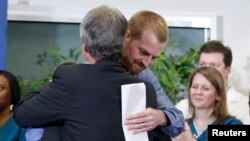 Kevin Brantly, (R) who contracted the deadly Ebola virus, hugs a member of Emory's medical staff during a press conference at Emory University Hospital in Atlanta, Georgia August 21, 2014.