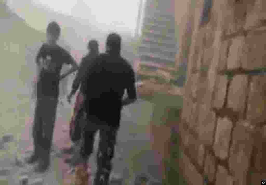 This image made from video provided by Shaam News Network (SNN) and accessed by the Associated Press on Tuesday, September 4, 2012 purports to show people walking through rubble after shelling in Idlib, Syria.