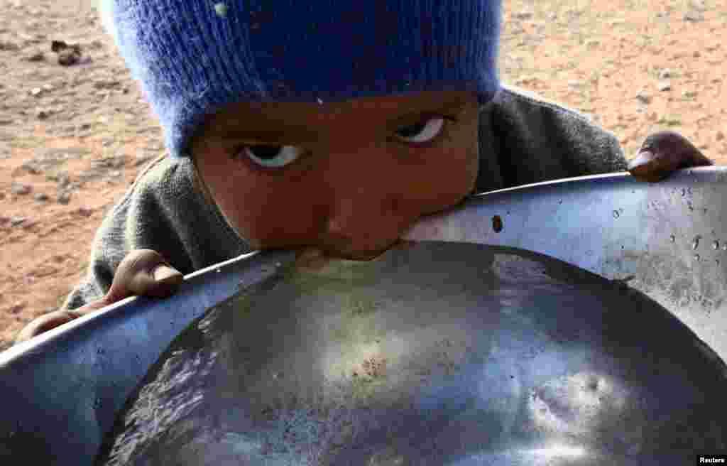 Seorang anak Arab yang tidak punya negara dari kelompok etnis yang dikenal sebagai Bedoon, yang dipercaya sebagai keturunan dari suku Badui nomaden, minum air dari panci di padang pasir barat dari wilayah Al-Jawf, Saudi Arabia.