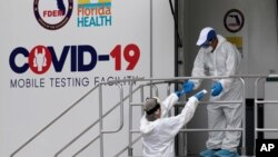 Health care workers work at a walk-up COVID-19 testing site during the coronavirus pandemic, Friday, July 17, 2020, in Miami Beach, Fla. The mobile testing truck is operated by Aardvark Mobile Health, which has partnered with the Florida Division of…