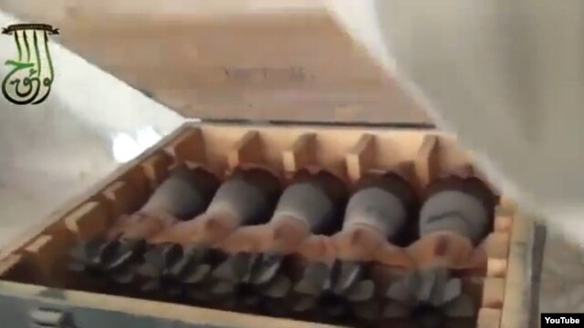 In this screen grab from a video posted to You Tube by Syrian activists, rebels who claim to have captured a government arm depot show crates rockets and other arms.