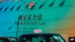 A taxi drives past a big banner featuring the Hong Kong National Security Law in Hong Kong, June 29, 2020.