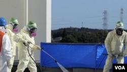 Para pekerja membersihkan atap kantor Okuma dari kontaminasi dekat pembangkit nuklir Fukushima Daiichi (4/12).