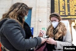 Women wearing protective masks disinfect their hands at the central railway station, after a coronavirus outbreak, in Milan, Italy, Feb. 24, 2020.