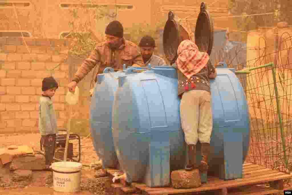 Keluarga-keluarga di Mosul mengumpulkan air dari sumur darurat yang dioperasikan dengan generator karena mereka tidak punya air yang mengalir atau listrik (2/12). (VOA/H.Murdock)