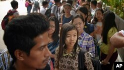 Myanmar citizens wait outside the Myanmar Embassy in Singapore to cast advance ballots on Oct. 18, 2015.