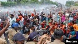 Pendukung Partai Bharatiya Janata Party (BJP) meneriakkan slogan saat polisi menembakkan meriam air untuk menghentikan perjalanan mereka menuju kantor pemimpin negara bagian Uttar Pradesh, Senin (2/5), memprotes perkosaan beramai-ramai di wilayah ini.