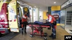英国两名救护人员在收治了一名被确诊为新冠病毒患者的 Son Espases 大学医院外做救护的准备工作。(2020年2月9日)