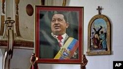 ພະນັກງານສະຖານທູດເວເນຊູເອລາ ທີ່ຄິວບາ ຍົກຮູບຂອງປະທານທິບໍດີ Hugo Chavez ທີ່ກໍາລັງປິ່ນປົວມະເຮັງ ຢູ່ໃນຄິວບາ.