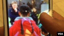 At a mall in Dresden, Germany, a man holds up a picture of the time he reported being attacked by locals, angry at the large influx of refugees and migrants. Since then he has been attacked again twice, but hasn't reported, July 8, 2016. (Photo: H. Murdo