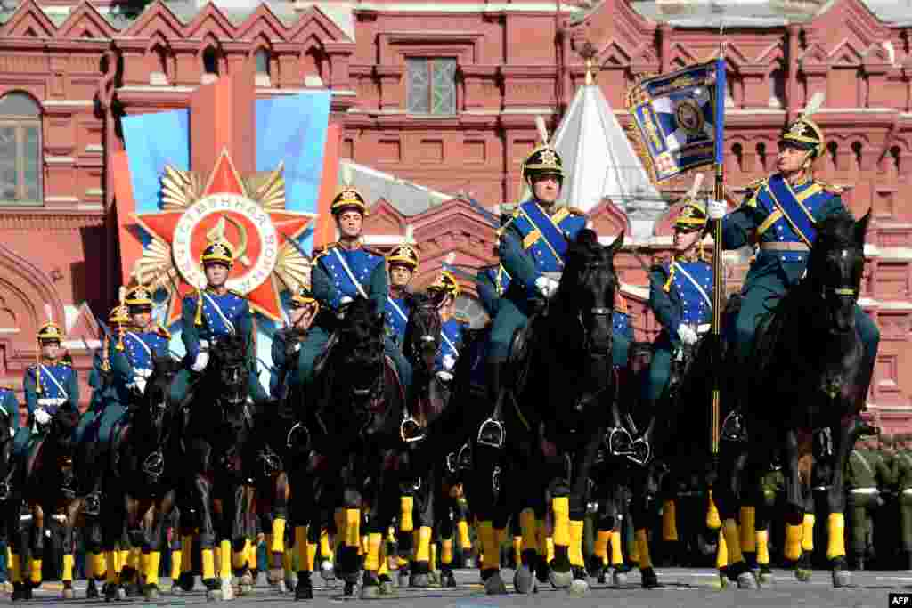 Russian honor guard troopers ride during a Victory Day parade at the Red Square in Moscow.