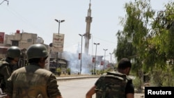 Syrian army soldiers run after a bomb exploded on a street in the town of Douma near Damascus, May 20, 2012.