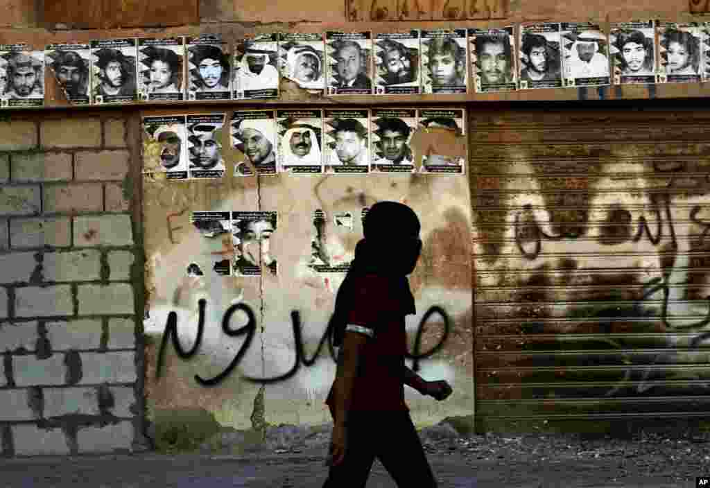 A masked Bahraini anti-government protester walks by a wall with posters honoring those who have died in recent unrest, during clashes with riot police in Sitra, Bahrain, Feb. 13, 2013.