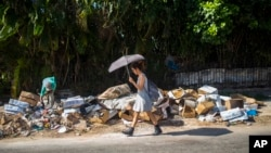 FILE - A woman walks by a pile of garbage in the Vedado neighborhood of Havana, Cuba, Oct. 20, 2018.