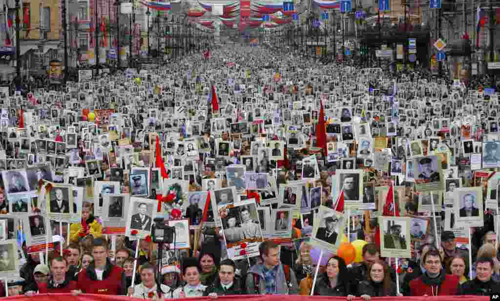 Local residents carry portraits of their ancestors, participants in World War II, as they celebrate Victory Day in St. Petersburg, Russia. About 30,000 people walked in the march named 'Immortal regiment.' Victory Day marks the defeat of Nazi Germany and is Russia's most important secular holiday.