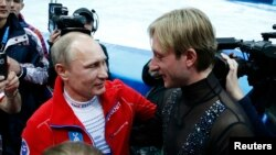 Russian President Vladimir Putin (L) greets Yevgeny Plushenko, a member of the gold medal-winning Russian figure skating team, during the 2014 Sochi Winter Olympics, Feb. 9, 2014.