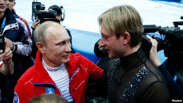 Russian President Vladimir Putin (L) greets Yevgeny Plushenko, a member of the gold medal-winning Russian figure skating team, during the 2014 Sochi Winter Olympics, Feb. 9, 2014.