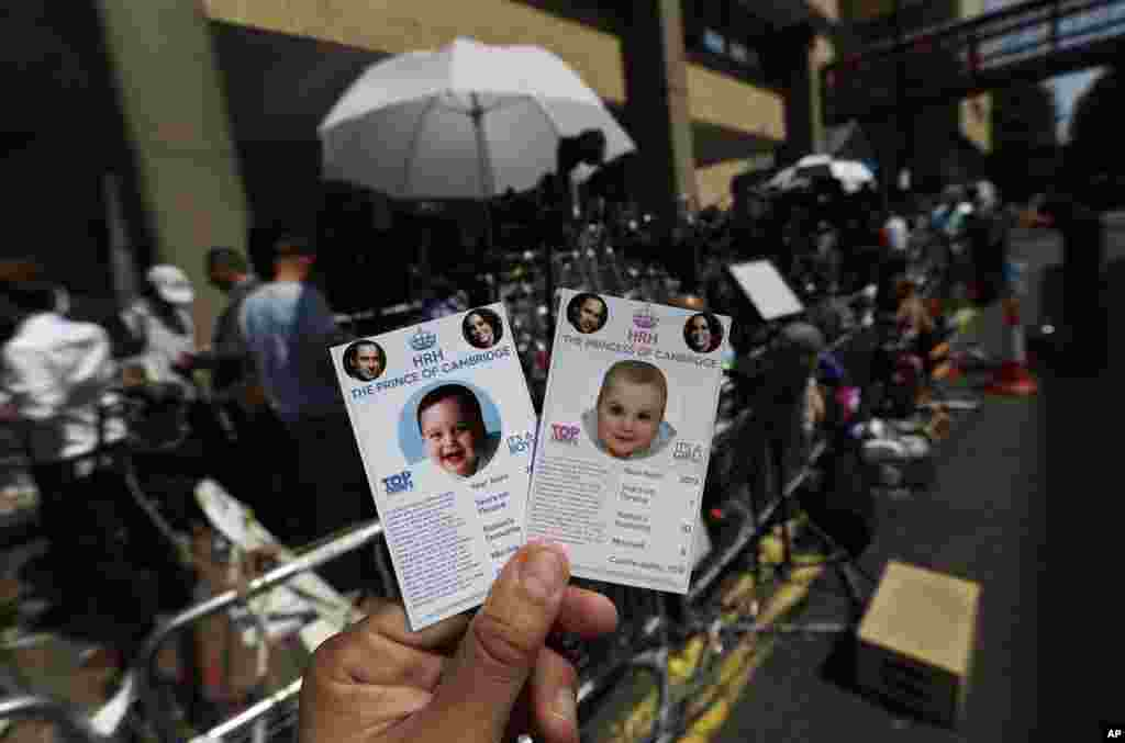 Cards depicting the 'royal baby,' either as a boy or a girl, made as a publicity stunt by a games company, are pictured. Members of the media waiting across from St. Mary's Hospital are seen in the background.